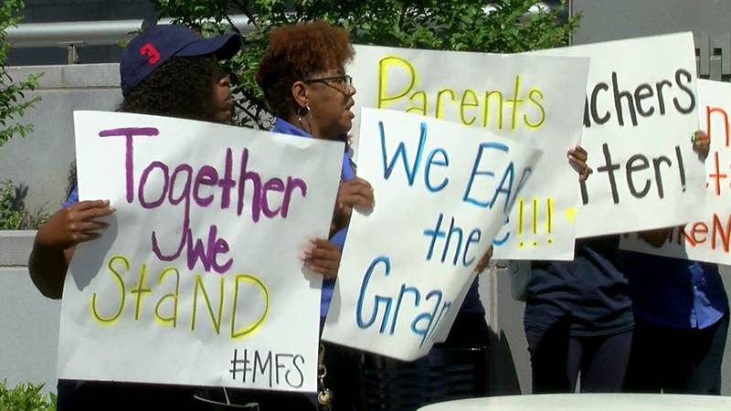Staff members with McMillian FIRST Steps hold signs protesting a decision by LSU Health-New...