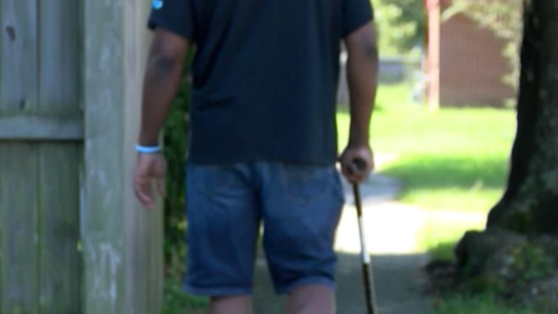 An African American male walks down a sidewalk.