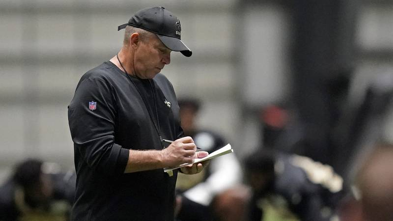 New Orleans Saints head coach Sean Payton takes notes during practice at their NFL football...