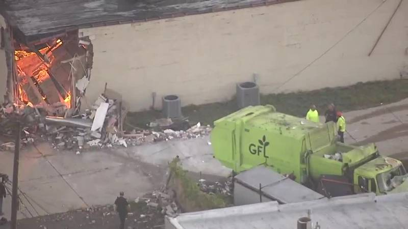 Surveillance video shows a garbage truck crashing into a building, hitting a trailer and...