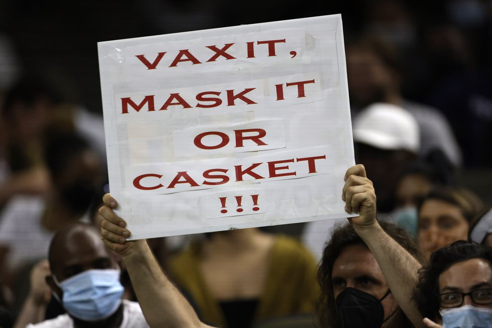 A fan holds up a sign in support of make wearing and vaccinations in the second half of an NFL...
