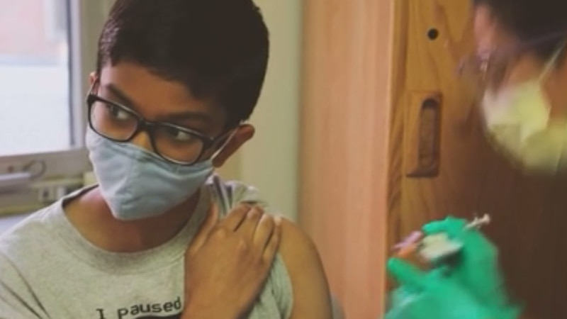 A young boy gets a vaccination shot.