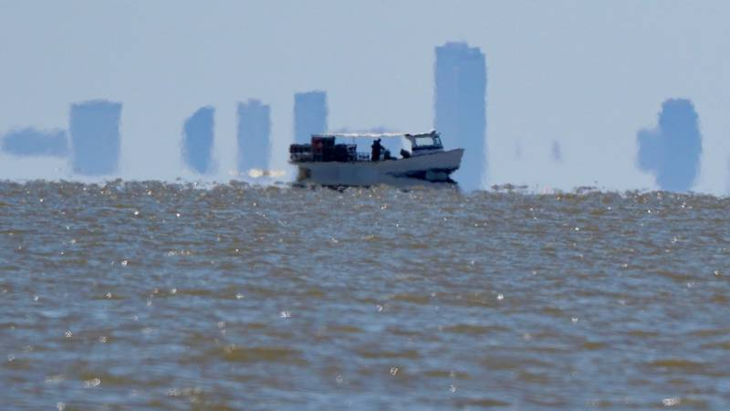 A crabber can be seen on Lake Pontchartrain with the New Orleans skyline in the distance