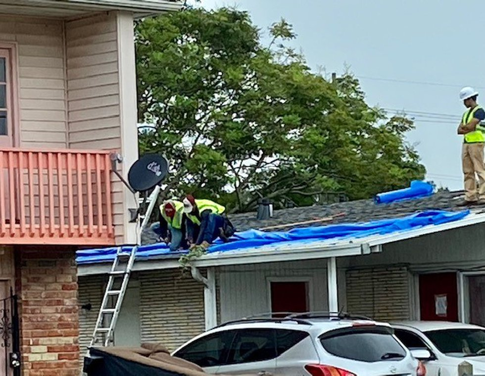 Crews who are part of the federal Blue Roof Program install tarp on a roof damaged by Hurricane...