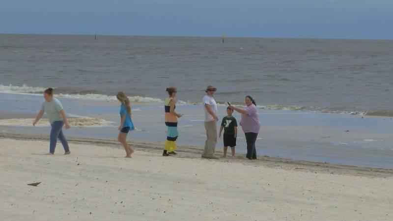Sharon Duncan, center, of Monroe, La.,  takes photos of her family in Biloxi on Monday.