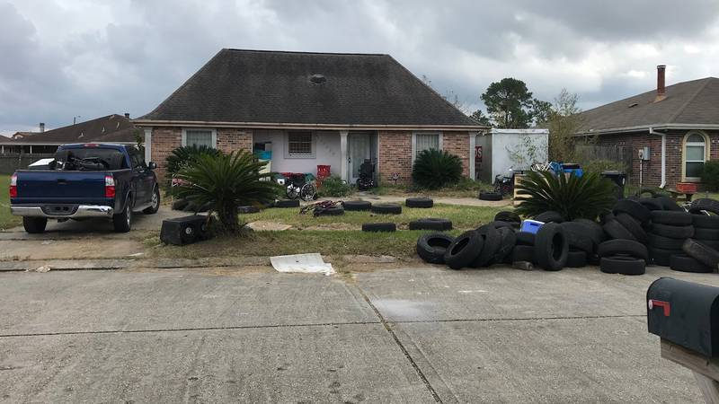 Dozens of old tires litter front lawn of New Orleans East home.