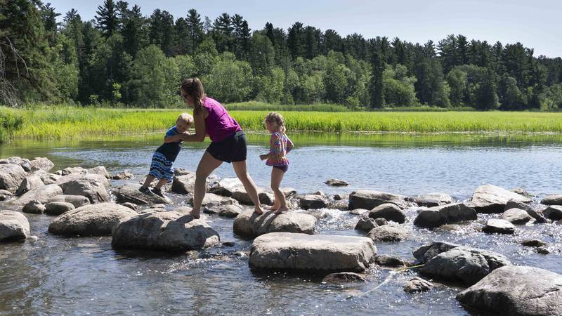 A woman helps children over rocks separating Lake Itasca from the Mississippi River at the...