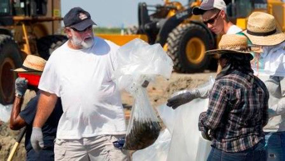 Workers place oiled mater recovered from Fourchon Beach inside plastic bags (John Snell)