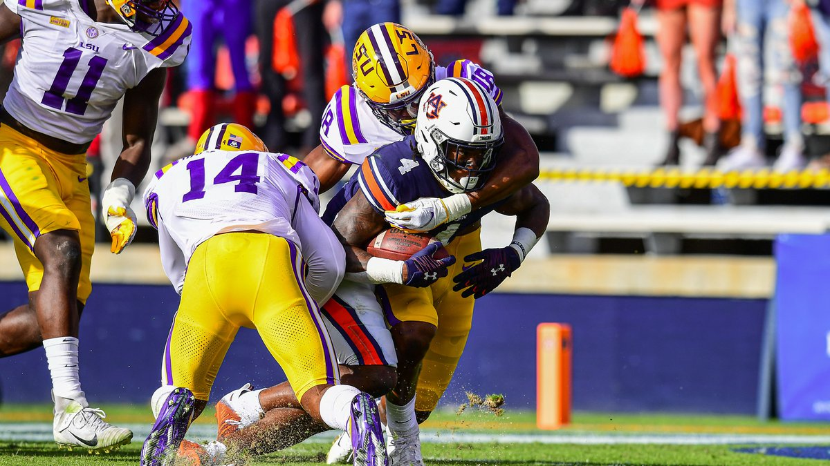 Damone Clark and Maurice Hampton Jr. of the LSU Tigers make a tackle during the first half of a...