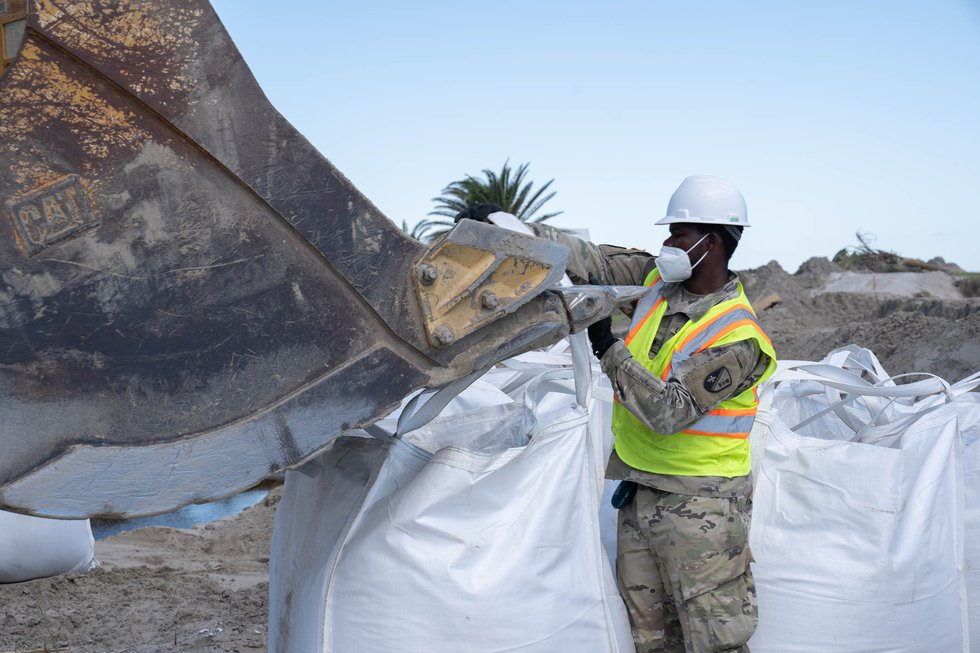 Louisiana National Guardsman assigned to the 225th Engineer Brigade hooks straps of a 3-by-3...