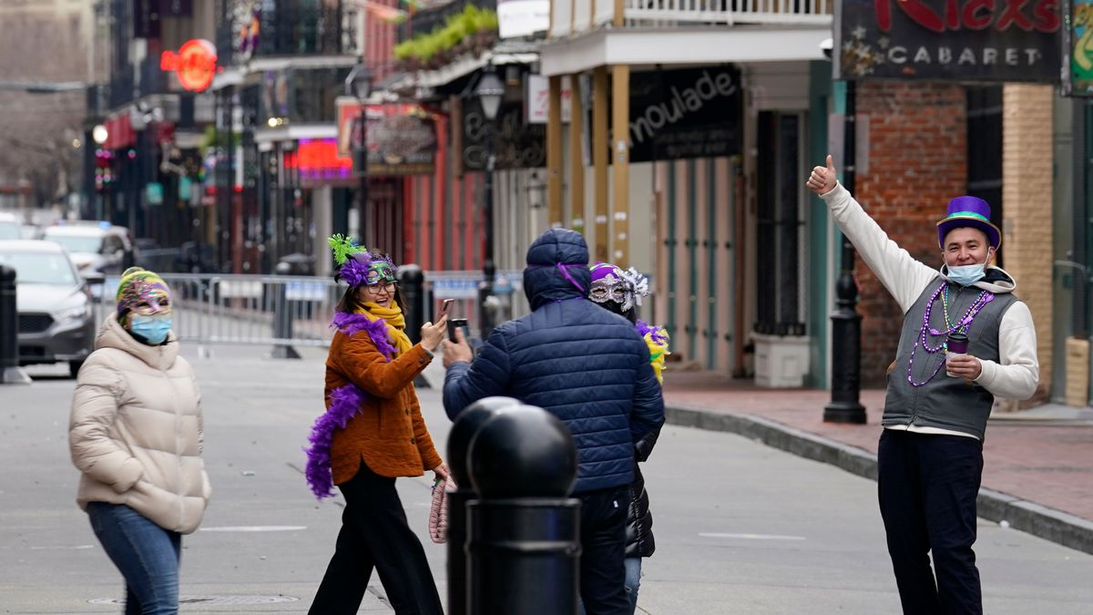 Tourists from Brooklyn take photos on a nearly deserted Bourbon Street during Mardi Gras in the...