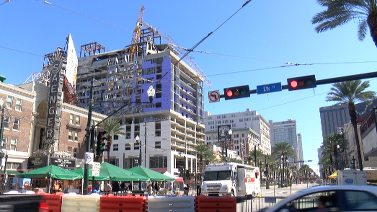 A portion of a damaged crane on the collapsed Hard Rock Hotel site continues to dangle over...