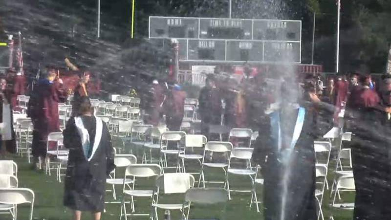 Sprinklers interrupted the in-person graduation ceremony Wednesday morning at Ashley Ridge High...