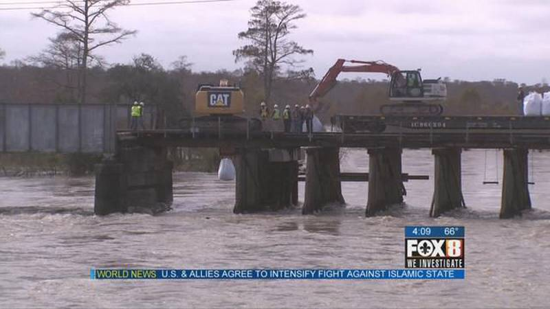 Railroad crews work to protect train bridge, near Bonnet Carre Spillway, from fast-moving water