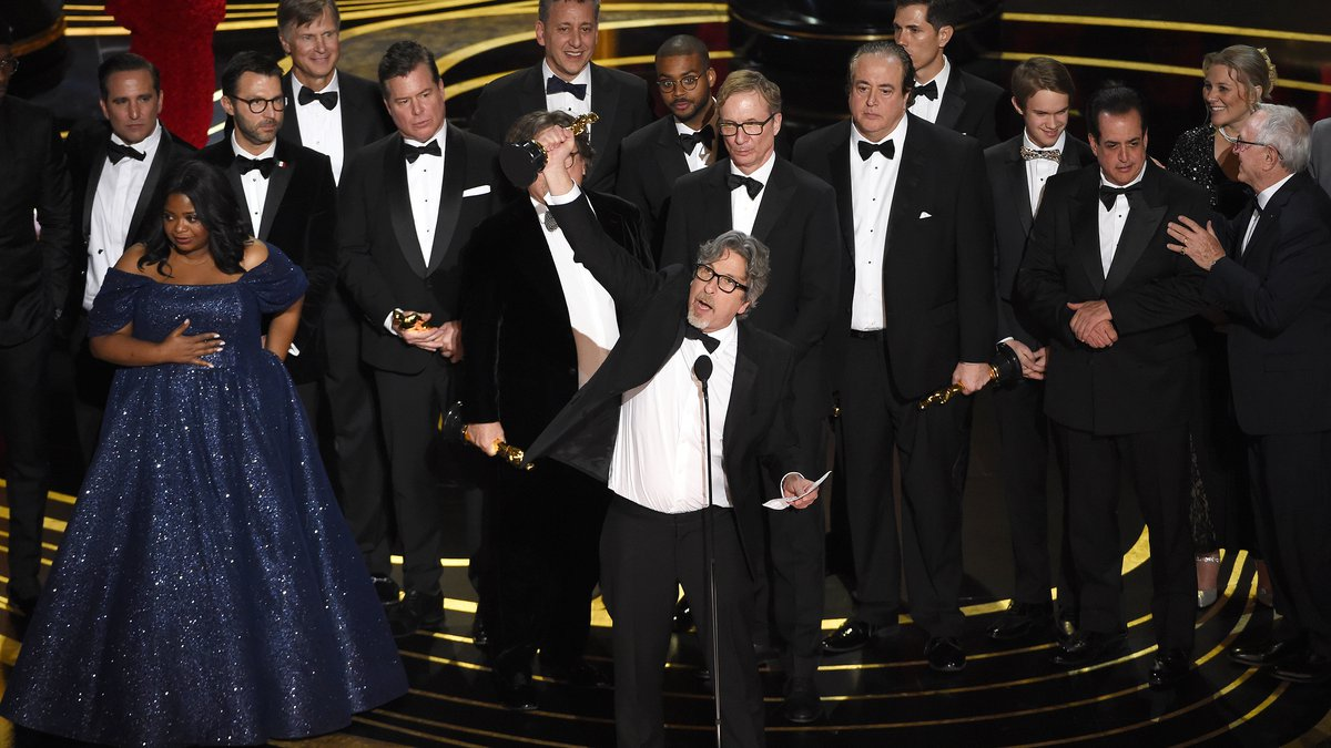 Peter Farrelly, center, and the cast and crew of Green Book accept the award for best picture...