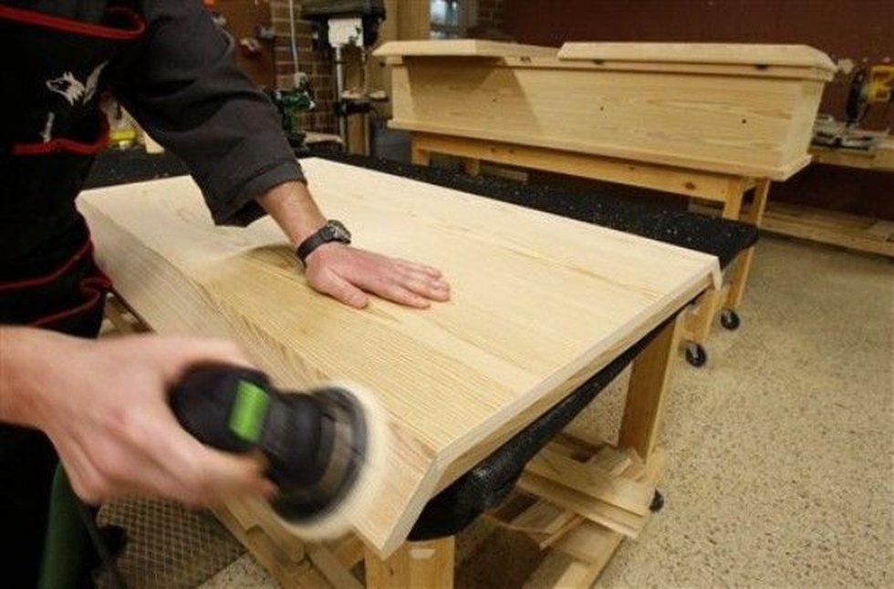 A worker sands a casket lid in a workshop at St. Joseph Abbey (File/AP Photo)
