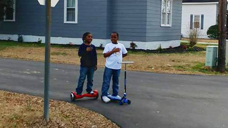 A picture of two boys from North Carolina stopping in a street to honor a U.S. flag as it was...