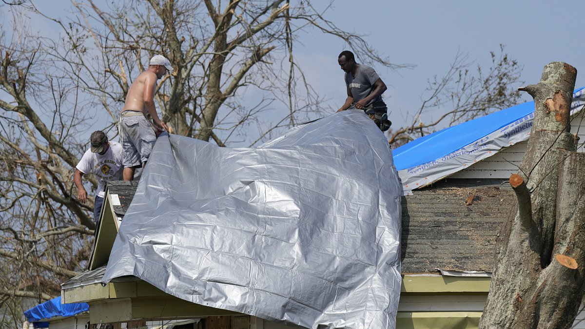 Gary Johnston, left, Grant Boughamer, center, and Jose Garcia, right, place a tarp on a roof...