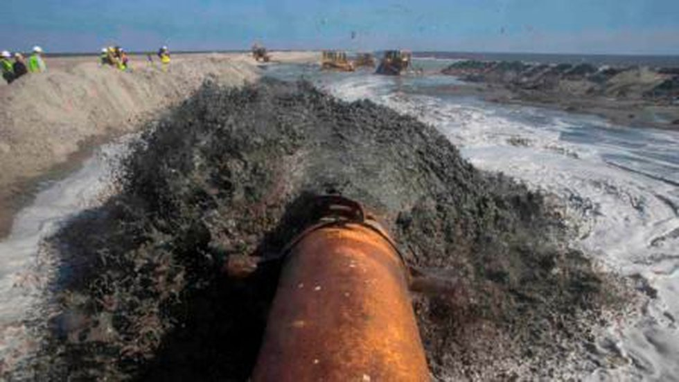 A pipe delivers sand to a new section of beach in the Caminada Headland (John Snell)