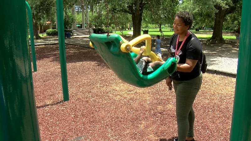 Sarah Perron pushes her toddler in a swing at City Park in New Orleans.