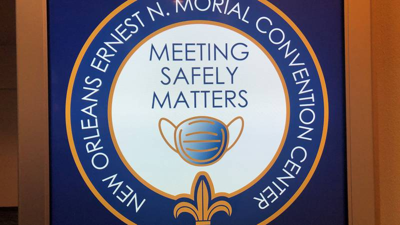 """""""Meeting safely matters"""" sign on monitors across the Morial Convention Center."""
